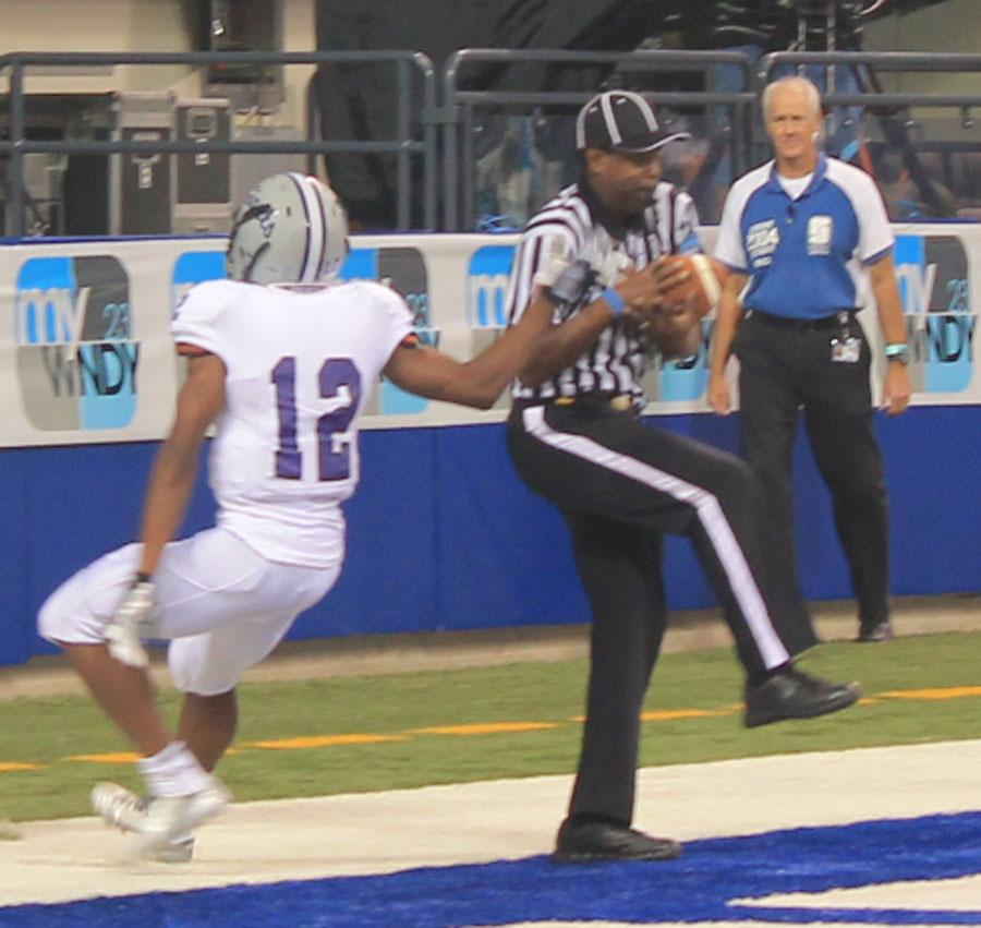 Sophomore Chris Evans hands the ball to the referee after scoring the game-winning touchdown with 50 seconds left.