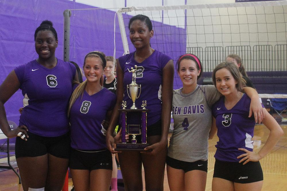 Senior volleyball players pose with the championship trophy.