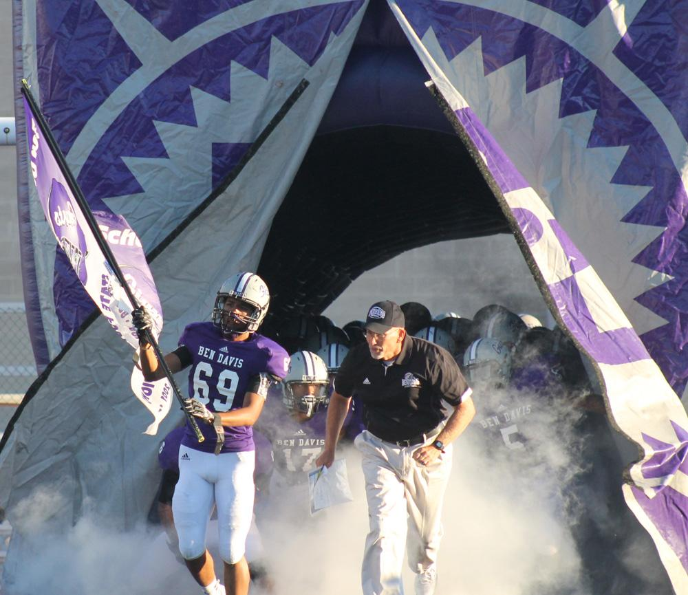 Senior Aaron Cazy and coach Mike Kirschner lead the team on to the field.