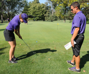 Assistant girls golf coach Bobby Chin watches junior Claire Thompson chip on to the practice green.