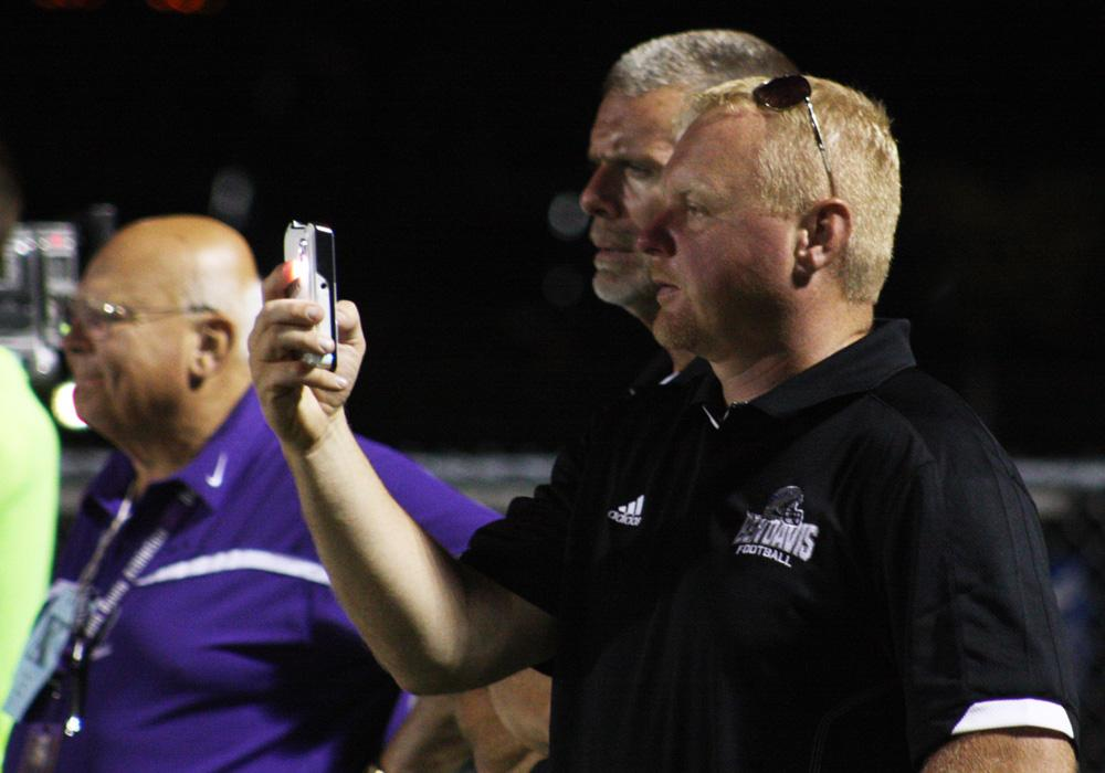 New assistant athletic director Doug Schornick takes a cell phone picture of the St. Xavier field Friday night in Cincinnati. Schornick is in his 13th season of helping with high school sports.