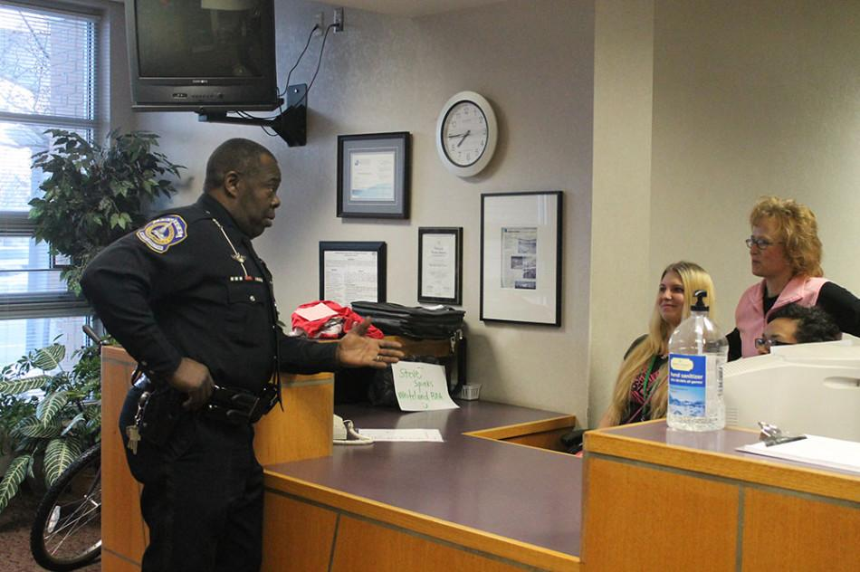 Officer Rex Singletary talks to the front office staff during first period.