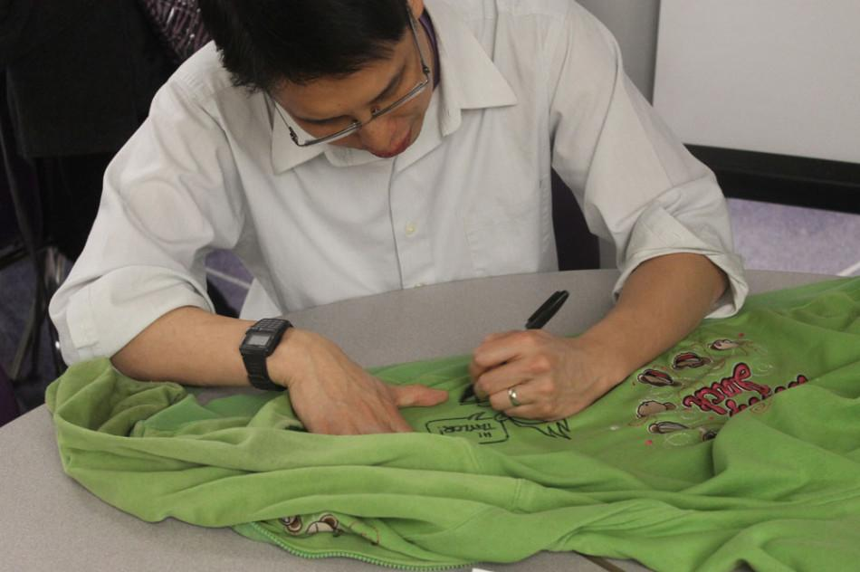 Author Gene Yang signs a sweatshirt during his March 13 visit to Ben Davis.