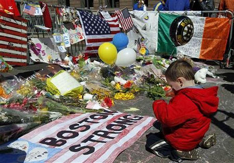 A child kneels at a memorial for victims of the Boston bombing that occcured during the 2013 running of the Boston Marathon.