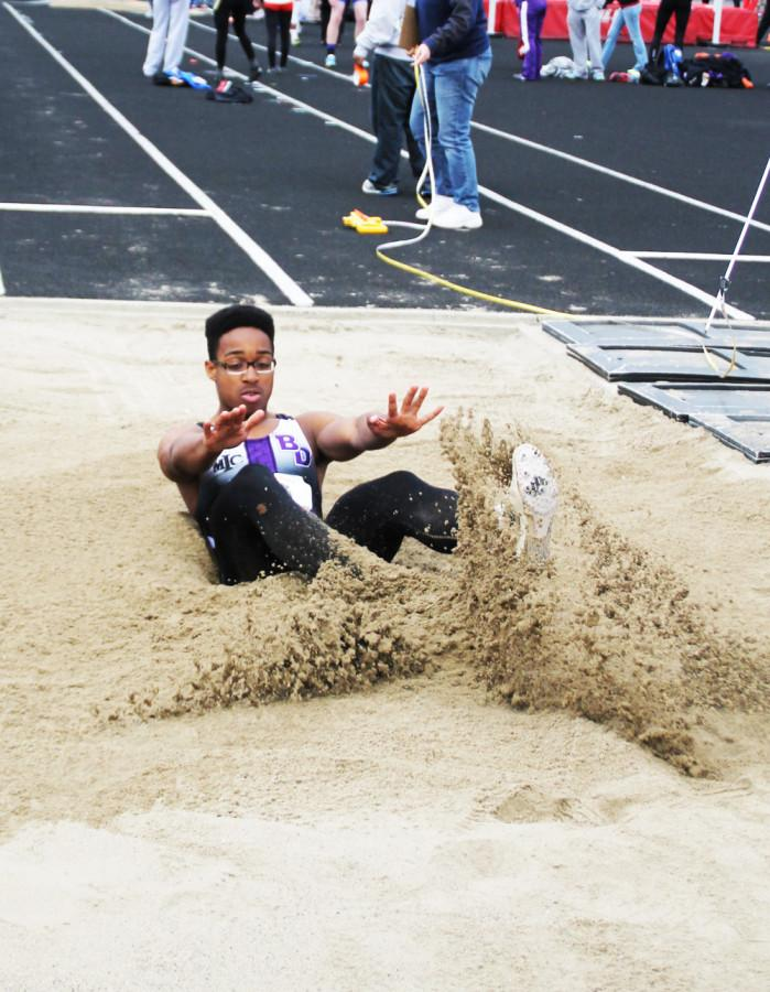 Sophomore Chris Evans lands in the long jump pit during the MIC meet Friday night. Evans finished third in the event.