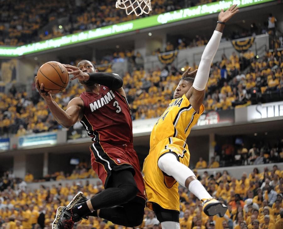 Miamis Dwayne Wade gets called for an offensive foul against Indianas Paul George Sunday afternoon at Bankers Life Fieldhouse.