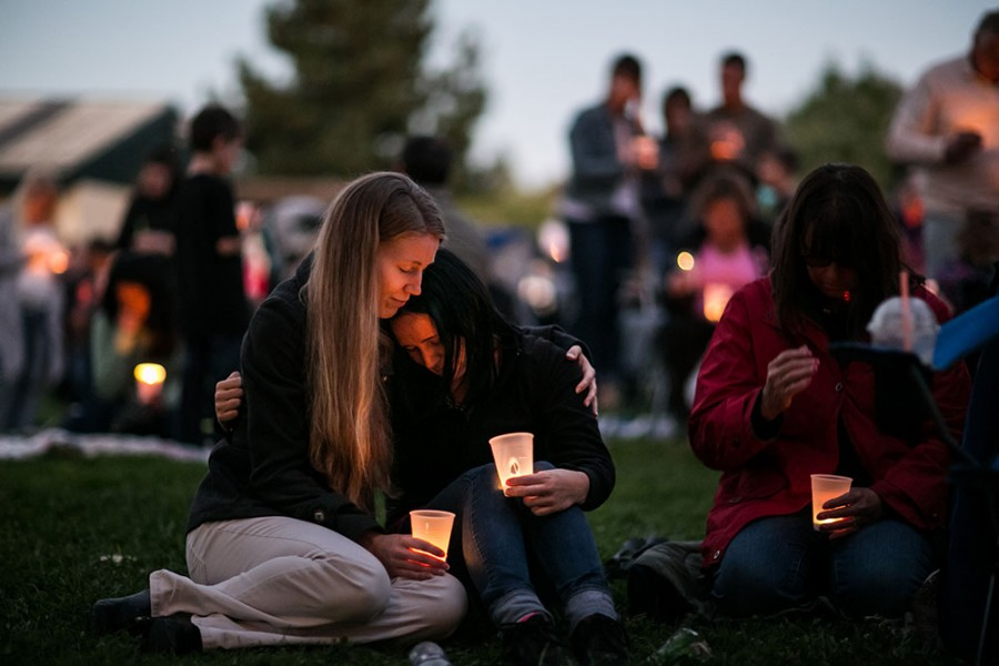 Heidi Wickersham, left, wipes away her tears while consoling her sister, Gwendolyn Wickersham, center, a UCC student who is grieving for her creative writing mentor, the slain Lawrence Levine, 67, a Umpqua Community College mass shooting victim, during candlelight vigil at a memorial service at Riverbend Park in Winston, Ore., on Saturday, Oct. 3.