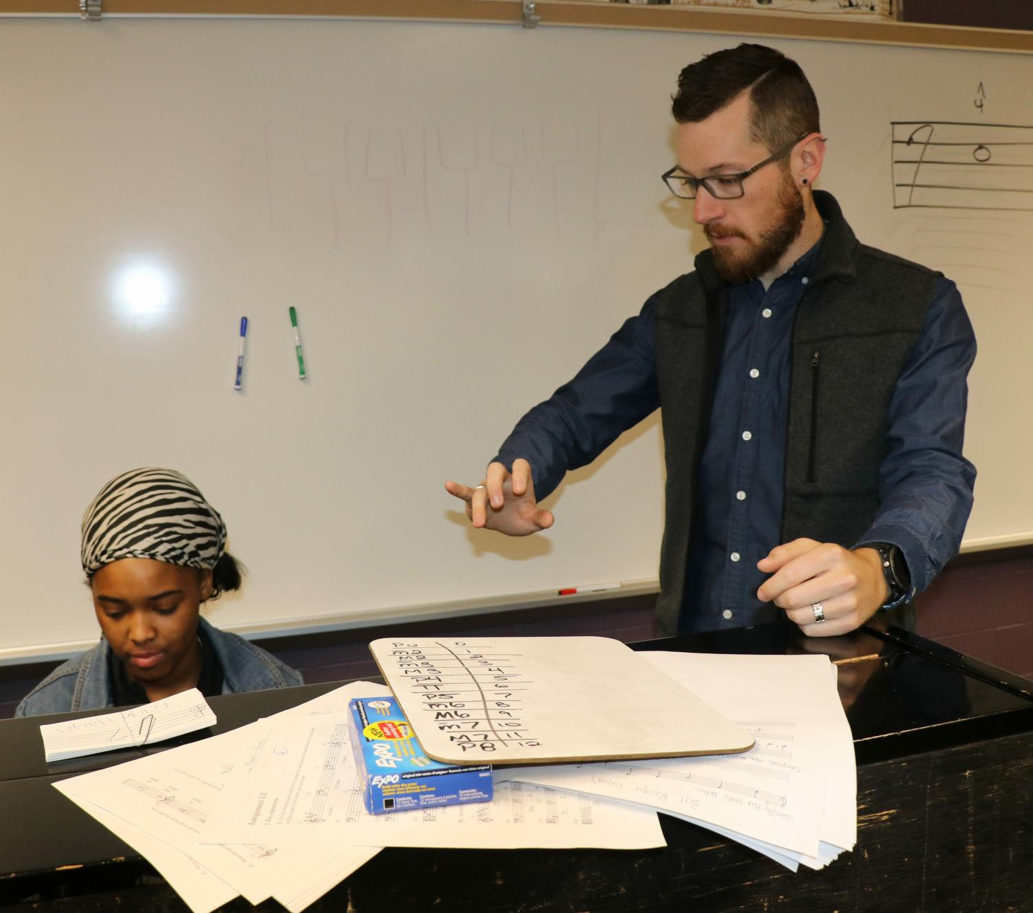 Jason David works with a student during music theory class.