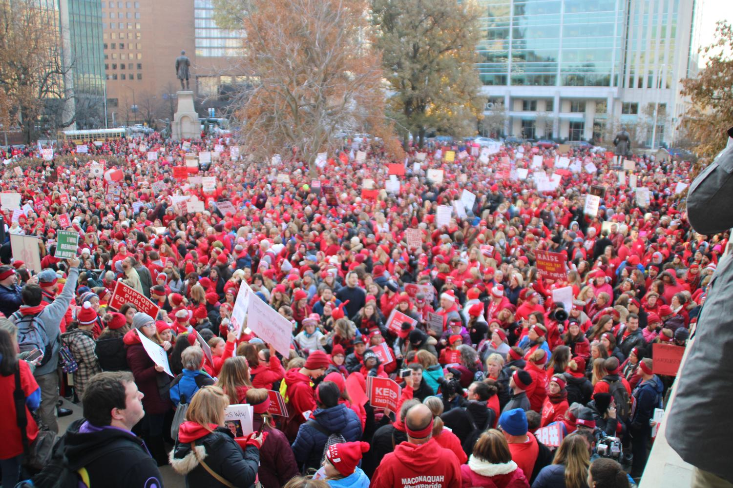 A crowd estimated at 15,000 gathers outside the Statehouse Tuesday morning at the RedforEd rally.