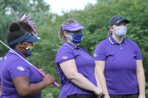 Members of the girls golf team protect themselves with clothe masks before the first meet of the season.